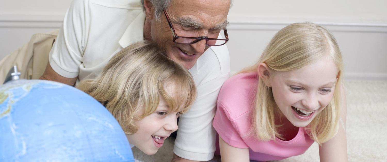 Opa mit Enkel und Globus schauen auf Landkarten